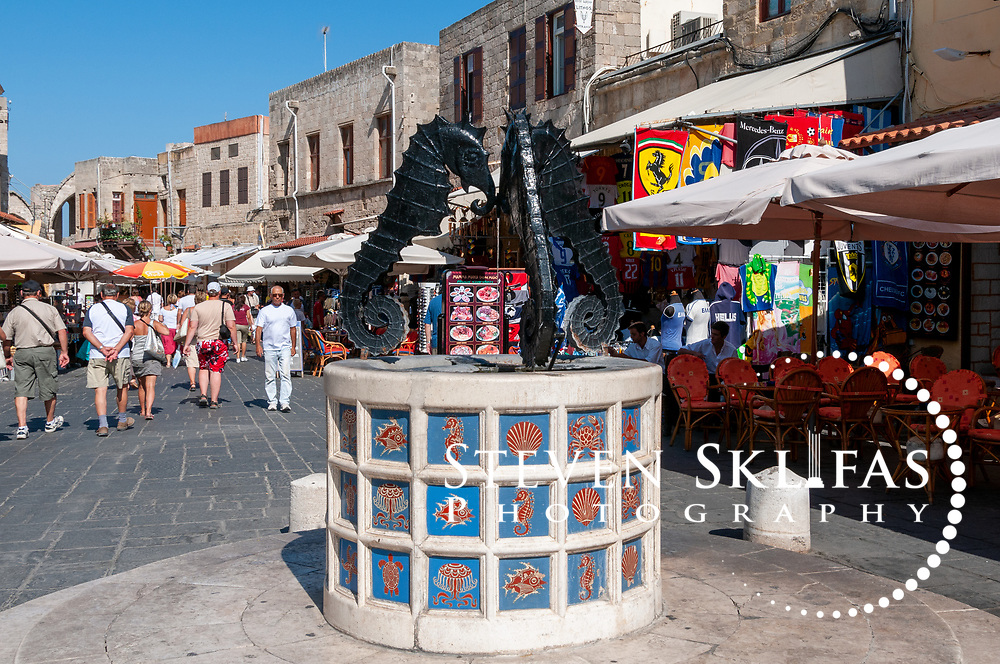 Rhodes. Greece. Little three seahorse fountain decked with images of marine life on blue tiles inside Rhodes old town. The fountain is located at the Square of Jewish Martyrs. The Square is part of the Jewish quarter inside the old walled town of Rhodes which is a UNESCO world heritage listed site and the best preserved, oldest and largest living medieval city in Europe.