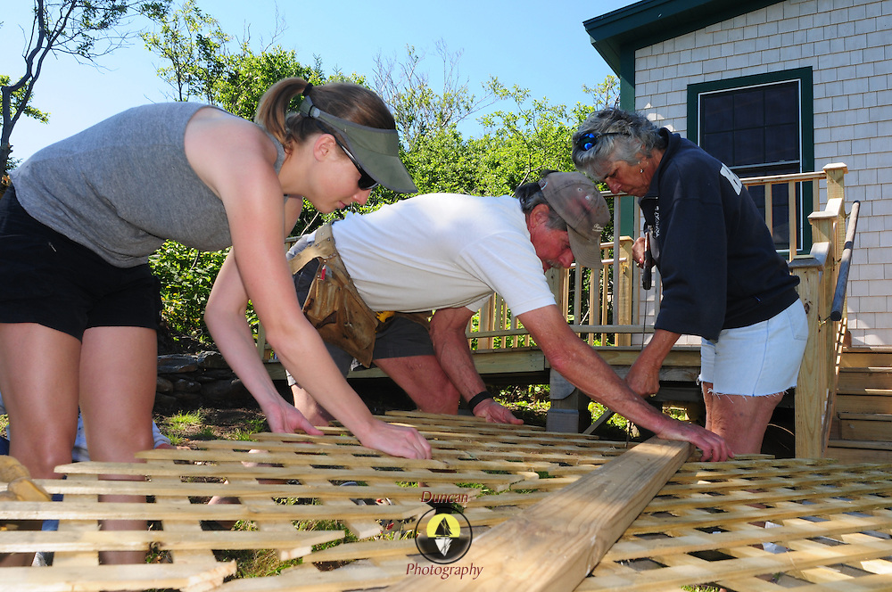EAGLE ISLAND, Maine -- June 23, 2014 -- Steve Ingram, center, lead volunteer with Friends of Eagle Island, assists a group of volunteers with construction at the island home of Adm. Robert Peary.  <br /> Photo © Roger S. Duncan for the Forecaster,  2014.