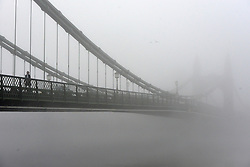 © Licensed to London News Pictures. 11/12/2013. London, UK. A woman walks across a fog covered Hammersmith Bridge.  Fog along the banks of the River Thames in Hammesmith, West London this morning 11th December 2013 . Photo credit : Stephen Simpson/LNP