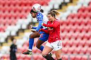 Reading forward Danielle Carter (18) wins a header with Manchester United defender Amy Turner (40 during the FA Women's Super League match between Manchester United Women and Reading LFC at Leigh Sports Village, Leigh, United Kingdom on 7 February 2021.