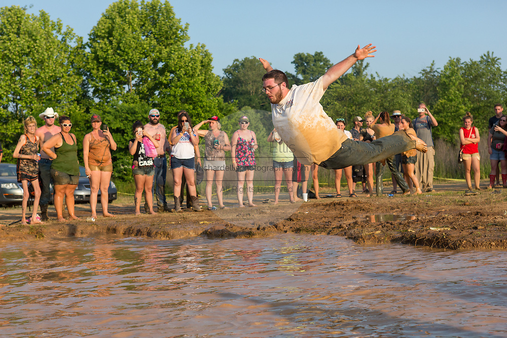 A competitor belly flops into a muddy watering hole during the dive competition at the 2015 National Red Neck Championships May 2, 2015 in Augusta, Georgia. Hundreds of people joined in a day of country sport and activities.