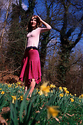 A911YA Low angle shot of young girl looking into the distance with daffodils in foreground