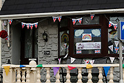 MERTHYR TYDFIL, WALES - 09 MAY 2020: House decorated with VE Day bunting, NHS rainbows,  and a Churchill sign in their window.