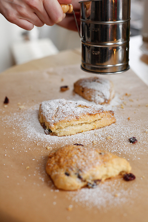 Orange-cranberry breakfast scones sprinkled with powdered sugar and glazed.