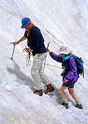 """A mountain guide from Robinson Expeditions escorts a client with rope and ice axe across a steep snow gully on a traverse of Mount Smolikas, second highest mountain in Greece. Hike the North Pindus Mountains (Pindos or Pindhos) around Zagoria, Epirus/Epiros, Greece, Europe. Zagori (Greek: ) is a region and a municipality in the Pindus mountains in Epirus, in northwestern Greece. Zagori contains 45 villages collectively known as Zagoria (Zagorochoria or Zagorohoria). Published in """"Pindos: The National Park"""" (2010) by Alexander G. Tziolas, preface by Tom Dempsey et al, ISBN 978-960-98795-3-8."""