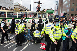 Metropolitan Police officers try to prevent Extinction Rebellion activists from locking on around a vintage bus used to block a road junction to the south of London Bridge on the ninth day of their Impossible Rebellion protests on 31st August 2021 in London, United Kingdom. Extinction Rebellion are calling on the UK government to cease all new fossil fuel investment with immediate effect.