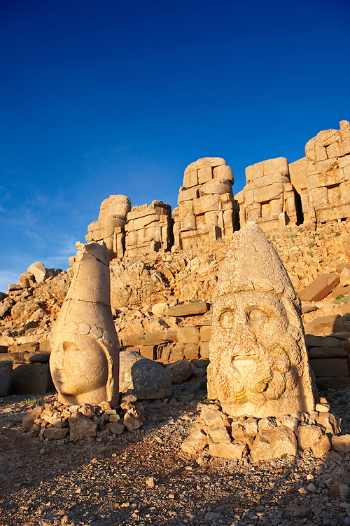 Image of the statues of around the tomb of Commagene King Antochus 1 on the top of Mount Nemrut, Turkey. Stock photos & Photo art prints. In 62 BC, King Antiochus I Theos of Commagene built on the mountain top a tomb-sanctuary flanked by huge statues (8–9 m/26–30 ft high) of himself, two lions, two eagles and various Greek, Armenian, and Iranian gods. The photos show the broken statues on the  2,134m (7,001ft)  mountain. 4