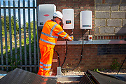 The big switch on next to an array of solar panels next to the line near Aldershot Railway Station on 23rd August 2019 in Aldershot, United Kingdom. This innovative project is the first in the UK to power the railway with electricity generated from solar power and, if successful, could see many Network Rail sites across the country adapting this sustainable energy approach. Riding Sunbeams is a social enterprise, run by 10:10 Climate Action. Built with Community Energy South and partnered with Network Rail and The Department for Transport and by InnovateUK.  Aldershot, Hampshire, United Kingdom. Riding Sunbeams is a world leading project to connect solar panels directly into electrified rail routes to power the trains. Direct supply of solar power to rail traction systems has never been done. But it has huge potential - from metros, trams and railways in the UK and around the world.