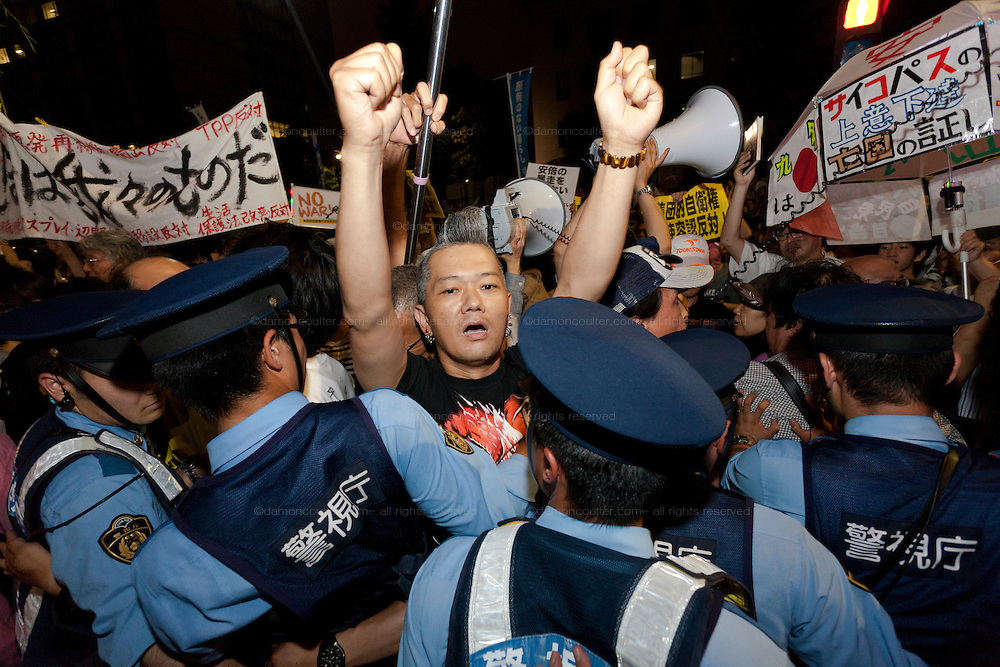 A young man with a Mohawk breaks the cordon and challenges police at a protest against the revision of article 9 of the Japanese Constitution outside the Prime-Minister's house in Kasumigasaki, Tokyo, Japan. Monday June 30th 2014. Over 10,000 people showed their support for Japan's unique peace constitution and called on the government to halt its reinterpretation of Article 9 allowing Collect Self Defence which is expected to become law on July 1st