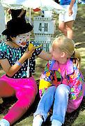 Asian girl as 4-H clown age 15 entertaining girl age 9 at Minnesota State Fair.  St Paul Minnesota USA