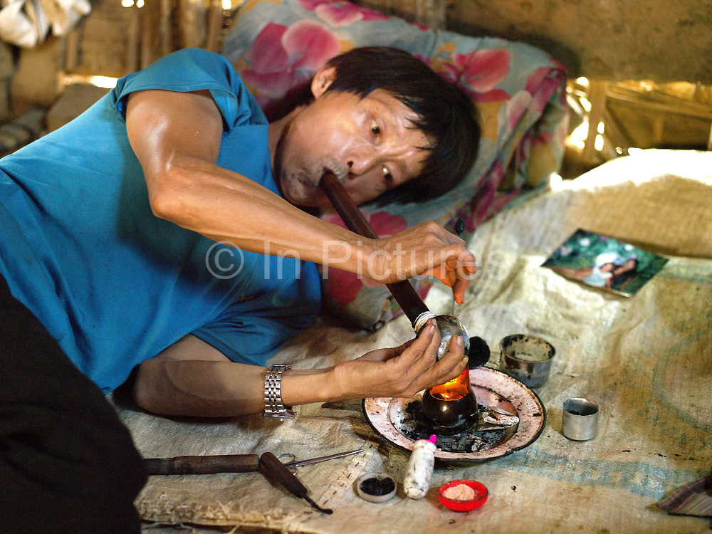 A Hmong ethnic minority man smokes opium at home in Lao PDR. Opium addicts are usually adult males. By taking opium, they lose the energy to work hard which leaves heavy tasks to women and children which then impoverishes the entire household. As recently as 1998, Lao PDR was the third largest illicit opium poppy producer in the world.  From 1998 to 2005, opium poppy cultivation in Lao PDR was reduced by 93 per cent.  In more remote areas where cash crops are not viable, surveys from UNODC have shown that between 2008 and 2012 the area under opium poppy cultivation has more than tripled. Although in 2013 the area of poppy fields in the country has again fallen, the number of regular opium users was still estimated at between 14,000 to 15,000 in the 10 northern provinces.