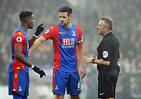 Football - 2016 / 2017 Premier League - Crystal Palace vs. Chelsea<br /> <br /> Wilfried Zaha of Crystal Palace makes his point to Referee J Moss as Captain Scott Dann steps in at Selhurst Park.<br /> <br /> COLORSPORT/ANDREW COWIE