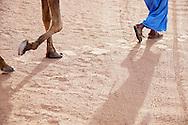 Legs of a walking man with dromedary in desert sand in the Sahara desert of Morocco.