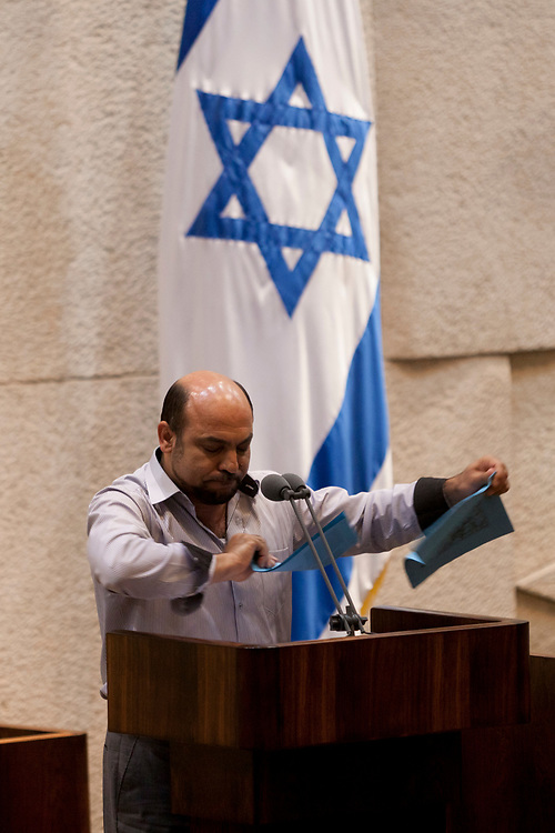 Arab-Israeli lawmaker, Member of the Knesset Masud Gnaim of the Ra'am-Ta'al party (acronym for United Arab List and Arab Movement for Renewal in Hebrew) tears the 'Praver Bill' in protest, during a debate on the bill, which is aimed at Bedouin settlements regularization in the Negev, at the Knesset, Israel's parliament in Jerusalem, on June 24, 2013. Arab-Israeli Knesset members tore the bill on the parliament's podium in protest of the proposed Bill which narrowly passed first reading.
