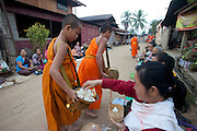 "Ban Saylom Village, just South of Luang Prabang, Laos. Every morning at dawn, barefoot Buddhist monks and novices in orange robes walk down the streets collecting food alms from devout, kneeling Buddhists. They then return to their temples (also known as ""wats"") and eat together. This procession is called Tak Bat, or Making Merit. ."