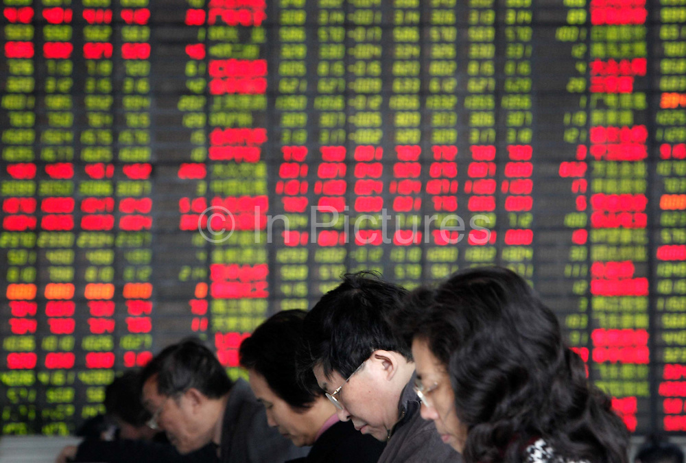 Investors check and trade stocks at a securities exchange house in Shanghai, China on 11 February, 2009.