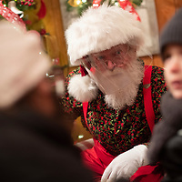 HAMMONTON, NJ:  A man dressed as Santa Claus wearing a face shield due to the coronavirus (COVID-19) pandemic greets children at DiDonato's Family Fun Center in Hammonton, NJ on December 6, 2020. Santa's Workshop is equipped with AirSoap filtration, which is said to kill and capture 99.99% of airborne viruses.  A family run business since 1952, DiDonato's holiday attraction features 5 million lights. The pandemic has forced difficult decisions about maintaining the holiday tradition of visits to Santa Claus versus safety concerns.  Plexiglass dividers, face shields, and physical distancing are among the precautions for those locations that have proceeded with Santa photo opportunities.  CREDIT:  Mark Makela for The New York Times