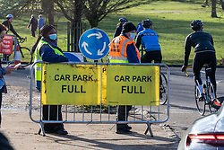 © Licensed to London News Pictures. 17/01/2021. London, UK. Security stand next to a car park full sign while members of the public enjoy a stroll in a very busy Richmond Park in South West London today as police keep up patrols in the parks. Earlier, the government pleaded with the public to stay at home as much as possible. And today, Foreign Minister Dominic Rabb said that lockdown could be lifted in March but with tier systems still in place as health chefs reveal that a 24/7 vaccination pilot will begin next week as total Covid-19 deaths reach over 88,000 this weekend. Photo credit: Alex Lentati/LNP
