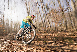 Mountain biker speeding on forest track in autumn
