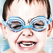 A child swimming in a pool with water filled swimming goggles.