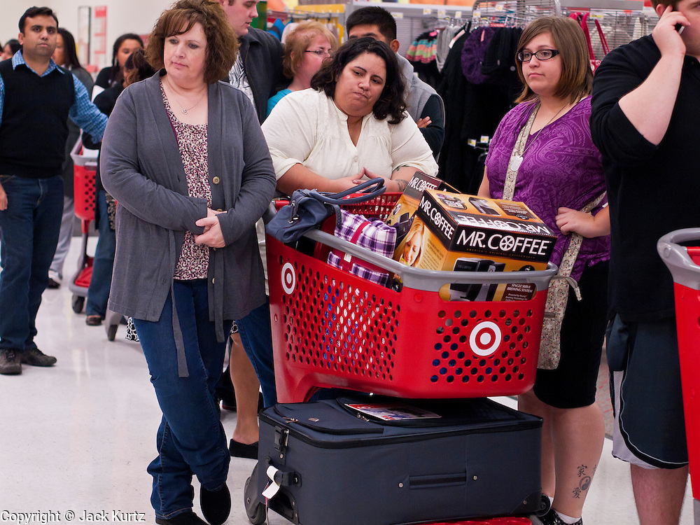 """25 NOVEMBER 2011 - PHOENIX, AZ:  01:25  L to R: Kelly Lloyd (CQ), from Phoenix, Oat Craig (CQ) from Maricopa and her daughter Samanth Craig (CQ) also from Maricopa, wait in line to check out in the Target Store across the street from Paradise Valley Mall Friday morning. """"Black Friday,"""" the unofficial start of the holiday shopping season started even earlier than normal. Many stores, including Target and Best Buy, opened at midnight.    Photo by Jack Kurtz"""