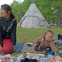 A reindeer-herding (Tsaatan) mother & her baby sell hand-made souvenirs to tourists visiting Lake Hovsgol and the Horidal Saridag Mountains in Mongolia's Hovsgol National Park. They live in the tipi tent in the background.