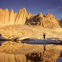 A hiker is reflected in a small lake below California's 14,505-foot Mount Whitney, highest peak in United States outside of Alaska.