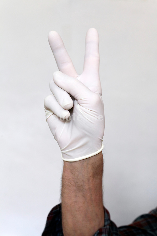 man with latex glove making the peace hand gesture