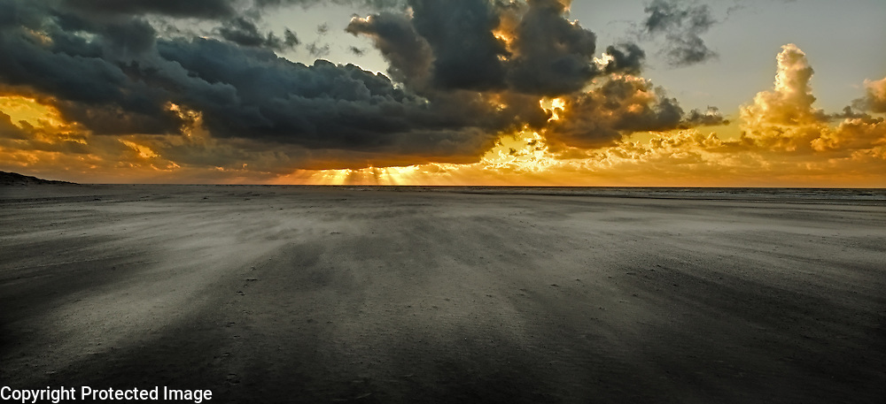 The wind blows streams of sand towards a spectacular sunset on the island of Texel, the Netherlands.