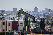 Oil well and pumpjacks in the City of Signal Hill with the City of Long Beach in the bacground. Once a massive oil producing area, oil wells are still mixed in its now residential neighborhoods. Los Angeles Coutny, California, USA