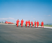 Pilots belonging to the elite 'Red Arrows', Britain's prestigious Royal Air Force aerobatic team, walk in line from their parked Hawk jet aircraft during their two-day visit to the airfield at the Payerne Air 04 show, Switzerland. It is a perfect day for aerobatics with blue alpine skies during the teams' two-day visit to the Swiss airfield. Payerne is home of the Swiss Air Force who host the cream of international aerobatic display flying every September to 275,000 spectators over a weekend. European display teams and air forces gathered to celebrate the 90th anniversary of Swiss military aviation. The team walk towards waiting transport wearing the red flying suits, synonymous with an ambassadorial role for the UK and recruiting tool for the RAF's pilots of the future. SInce their birth in 1965, they have performed over 4,000 shows in 52 countries. .