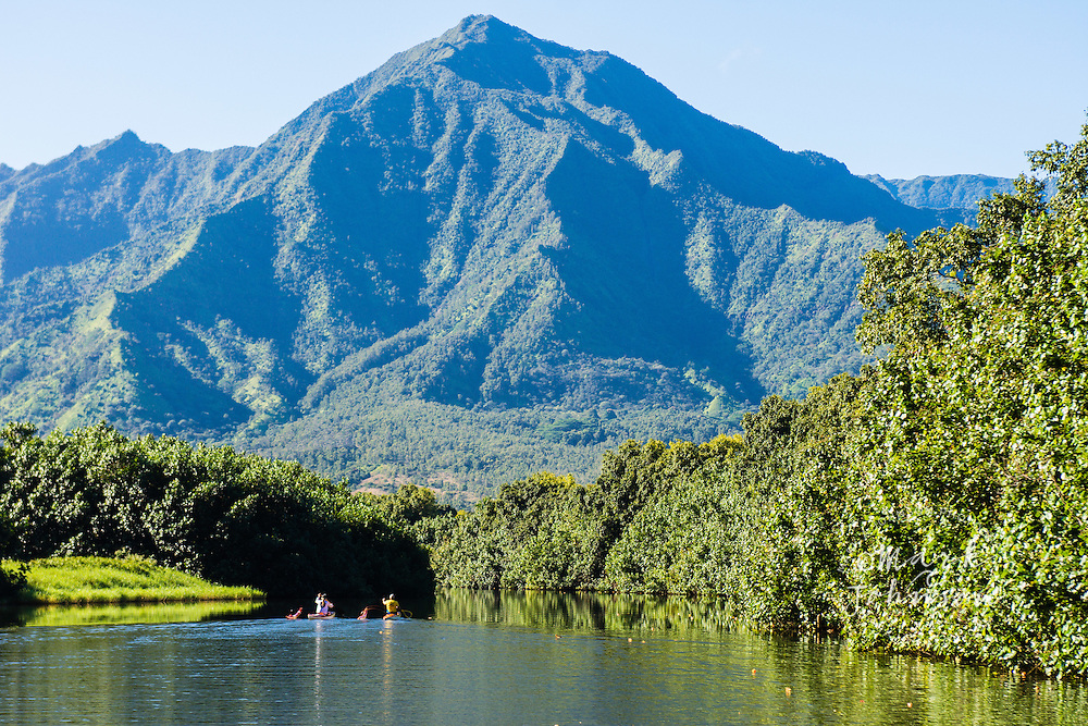 2 women paddling their one-woman outrigger canoes on the Hanalei River, Kauai, Hawaii