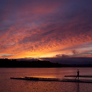 A rower stretches before rowing during a beautiful sunrise on Lake Karapiro, near Cambridge, Waikato. Many national and international rowing competitions are held on Lake Karapiro which is also the home of The Rowing New Zealand High Performance Centre. Lake Karapiro hosted the 2010 World Rowing Championships. Lake Karapiro, Waikato,  New Zealand. 15th December 2010. Photo Tim Clayton