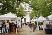 People stroll through an outdoor art market and sale at the Second Presbyterian Church on Wragg Square in the historic district May 29, 2021 in Charleston, South Carolina.
