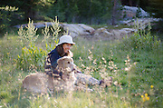 Woman and her dog sitting in an alpine meadow, Carson-Iceberg Wilderness, Stanislaus National Forest, California