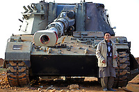 A local resident stands next to a tank belonging to pro-Ghaddafi forces that was devastated by at a staging area outside Benghazi that was devastated by coalition forces enforcing the no-fly zone over eastern Libya