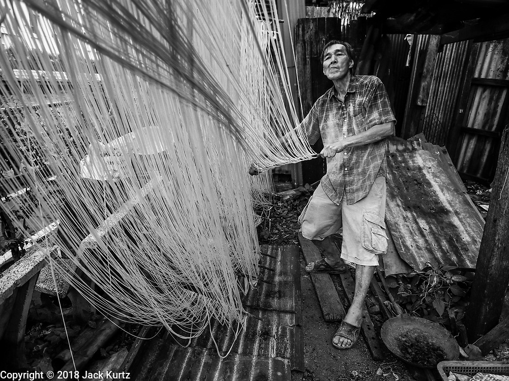 "29 DECEMBER 2018 - BANGKOK, THAILAND: A man stretches longevity noodles in front of his family shophouse. The family has been making traditional ""mee sua"" noodles, also called ""longevity noodles"" for three generations in their home in central Bangkok. They use a recipe brought to Thailand from China. Longevity noodles are thought to contribute to a long and healthy life and  are served on special occasions, especially Chinese New Year, which is February 4, 2019. These noodles were being made for Chinese New Year.    PHOTO BY JACK KURTZ"