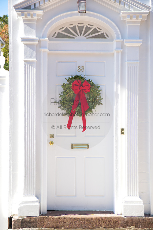 Door on a traditional home decorated with a Christmas wreath in Charleston, SC.