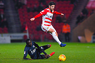 Danny Andrew of Doncaster Rovers (3) skips over a tackle from Elvis Bwomono of Southend United (2) during the EFL Sky Bet League 1 match between Doncaster Rovers and Southend United at the Keepmoat Stadium, Doncaster, England on 12 February 2019.