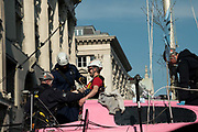 Police removing and arresting a climate protester who was glued onto the mast of the boat. In an operation that took several hours, Police removed the pink boat named Berta Caceres after the Hondruan nun who was murdered for being an environmental activist, that was the centrepiece of Extinction Rebellions site. It involved people who were locked on being removed. Several roads were blocked across four sites in central London, by the Extinction Rebellion climate change protests, April 2019.