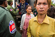 16 JUNE 2014 - POIPET, CAMBODIA: Cambodian migrant women walk away from a Thai immigration police vehicle after they were brought back to Poipet, Cambodia from Thailand. More than 150,000 Cambodian migrant workers and their families have left Thailand since June 12. The exodus started when rumors circulated in the Cambodian migrant community that the Thai junta was going to crack down on undocumented workers. About 40,000 Cambodians were expected to return to Cambodia today. The mass exodus has stressed resources on both sides of the Thai/Cambodian border. The Cambodian town of Poipet has been over run with returning migrants. On the Thai side, in Aranyaprathet, the bus and train station has been flooded with Cambodians taking all of their possessions back to Cambodia.  PHOTO BY JACK KURTZ