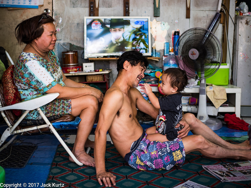 """08 FEBRUARY 2017 - BANGKOK, THAILAND: A family that makes artisan bird cages relax with their son in their home in Pom Mahakan. The residents of the old fort are known for their community of song bird enthusiasts. More than 40 families still live in Pom Mahakan, a slum community in a 19th century fort in Bangkok. City officials are trying to move them out of the fort but members of the community refuse to leave. NGOs and historic preservation organizations are working with the community to help them find a way to stay. After several deadlines passed, residents were told that they have to leave by the end of February. They submitted another proposal to the city this week to turn their community into a """"living heritage museum"""" and hope to get the eviction deadline extended until late March.       PHOTO BY JACK KURTZ"""