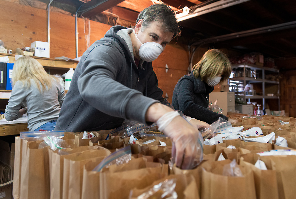 """YARMOUTH PORT - Steve Dalin and Kathy Kuck place cookies baked by the Hyannis Garden Club in bagged lunched for the homeless at Harvest of Cape Cod. Store owner Pamela Parker has temporarily closed her home decor retail store because of Gov. Baker's shutdown of """"nonessential"""" businesses. She's still open online but in the midst of all this uncertainty, she decided to make space in her warehouse to put together these meals since there is a gap in meal services for the food insecure on the weekend. She and her employees have put together over a hundred bagged meals and dropped them off at Saint Joseph House shelter in Hyannis."""