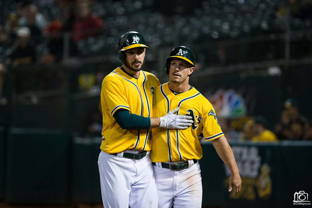 Oakland Athletics left fielder Matt Joyce (23), left, and Oakland Athletics center fielder Boog Powell (3) walk back to the dugout in between innings against the Los Angeles Angels at Oakland Coliseum in Oakland, California, on September 5, 2017. (Stan Olszewski/Special to S.F. Examiner)