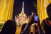 """30 JANUARY 2013 - PHNOM PENH, CAMBODIA:    People use their smart phones to photograph the crematorium for late Cambodian King Norodom Sihanouk in Phnom Penh. Sihanouk (31 October 1922- 15 October 2012) was the King of Cambodia from 1941 to 1955 and again from 1993 to 2004. He was the effective ruler of Cambodia from 1953 to 1970. After his second abdication in 2004, he was given the honorific of """"The King-Father of Cambodia."""" Sihanouk held so many positions since 1941 that the Guinness Book of World Records identifies him as the politician who has served the world's greatest variety of political offices. These included two terms as king, two as sovereign prince, one as president, two as prime minister, as well as numerous positions as leader of various governments-in-exile. He served as puppet head of state for the Khmer Rouge government in 1975-1976. Most of these positions were only honorific, including the last position as constitutional king of Cambodia. Sihanouk's actual period of effective rule over Cambodia was from 9 November 1953, when Cambodia gained its independence from France, until 18 March 1970, when General Lon Nol and the National Assembly deposed him. Upon his final abdication, the Cambodian throne council appointed Norodom Sihamoni, one of Sihanouk's sons, as the new king. Sihanouk died in Beijing, China, where he was receiving medical care, on Oct. 15, 2012. His cremation is scheduled to take place on Feb. 4, 2013. Over a million people are expected to attend the service.        PHOTO BY JACK KURTZ"""