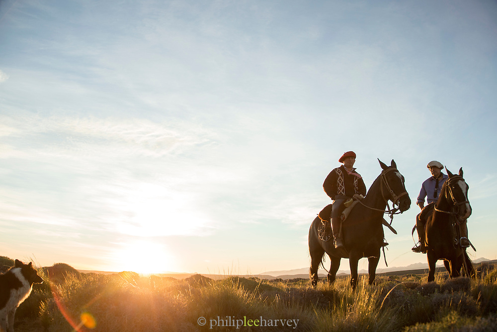 Gauchos on horseback cross the plain, Estancia Huechahue, Patagonia, Argentina, South America