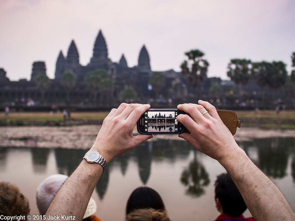 """14 MARCH 2105 - SIEM REAP, SIEM REAP, CAMBODIA: A tourist photographs Angkor Wat with his smart phone at sunrise. The area known as """"Angkor Wat"""" is a sprawling collection of archeological ruins and temples. The area was developed by ancient Khmer (Cambodian) Kings starting as early as 1150 CE and renovated and expanded around 1180CE by Jayavarman VII. Angkor Wat is now considered the seventh wonder of the world and is Cambodia's most important tourist attraction.   PHOTO BY JACK KURTZ"""