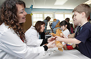 Jacqueline Sullivan of Excel Urgent Care hands a teddy bear back to Scotchtown Avenue Elementary School kindergarten student Matthew Barbrack during a Teddy Bear Clinic at the school in Goshen on Wednesday, April 14, 2010. Staff from Excel Urgent Care examined and treated injured stuffed animals at the clinc. The children also got to sit inside an ambulance from Mobile  Life Support Services. The program, now in its second year of visiting elementary schools in the Hudson Valley, is designed to make the children more comforatable with medical care.