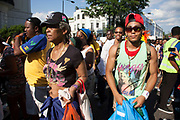 The 49th Notting Hill Carnival in West London. A celebration of West Indian / Caribbean culture and Europe's largest street party, festival and parade. Revellers come in their hundreds of thousands to have fun, dance, drink and let go in the brilliant atmosphere. Black males walking the parade route.
