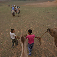 Children lead camels carrying tourists in the Gobi Desert, Mongolia.